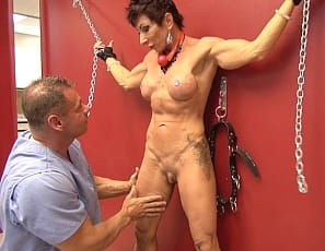 Female muscle pornstar Anna Phoenixxx is being put through what must be the strangest strength training exercise ever. She is restrained with chains and soon finds her big clit at the mercy of some strange clinical examiner. We are not going to complain about seeing Anna's ripped abs, big biceps, and sweet wet pussy, but we have to wonder just what in the hell is going on here?!