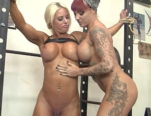 Tattooed Dani Andrews ties female bodybuilder Megan Avalon up in the gym to help her train more effectively, and they enjoy some girl/girl play as Dani fondles Megan's muscular pecs, biceps, ripped abs and legs and investigates what's in her panties. Watch the muscle fucking in close-up.