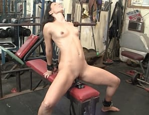 Tattooed, flexible Wenona is strapped to a bench in the gym, but discovers a toy there and penetrates herself with it. Watch her masturbate, and enjoy her muscular legs and glutes in close-up.