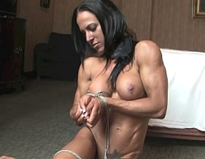 Female muscle porn star Rachel is tied up in her bedroom, but she frees herself and poses nude for you, showing off her tattoos and the mature muscles of her pecs, legs, glutes, biceps and abs, and plays with her pussy while you watch in close-up.