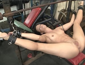 Tattooed, flexible female muscle porn star Wenona's chained up naked and barefoot in the gym, her muscular legs,  glutes, and pussy spread wide. You get to watch in close-up as she struggles.
